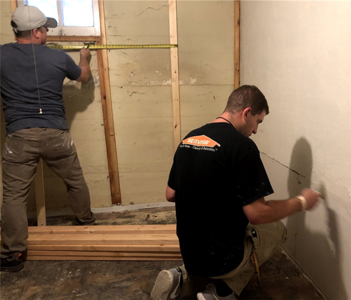Two men in a house. both are creating measurements on a wall using a tape measurer