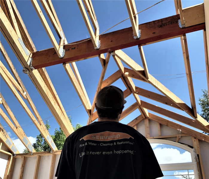 a man standing in a home with no roof during mid construction