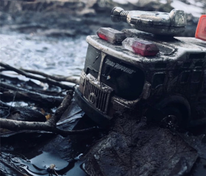 a small firetruck toy that has been charred with smoke and soot damge