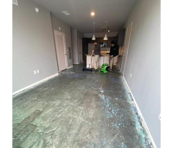 2 men removing adhesive from underneath flooring