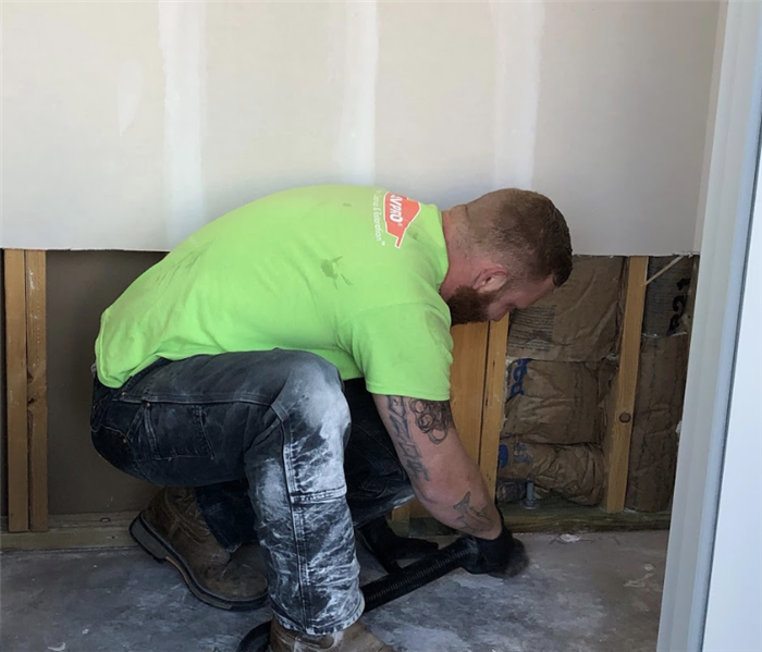 a SERVPRO worker vaccuming along the baseboards