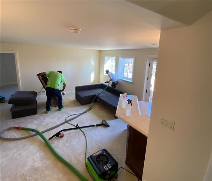 Two team members removing water in living room area.
