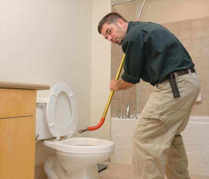 "A plumber with a tool called ""snake"" trying to push out any blockage on a toilet"