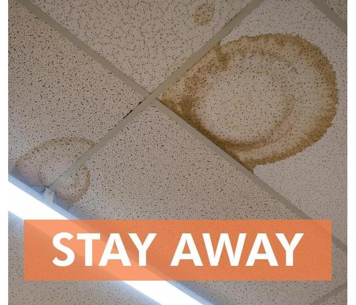 Ceiling tile stained and words that say STAY AWAY