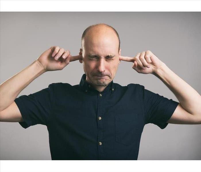 Bald man covering his ears over gray background