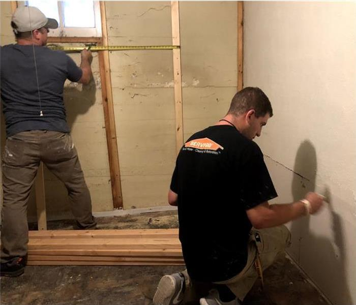 Two SERVPRO technicians assessing a water damage inside a home