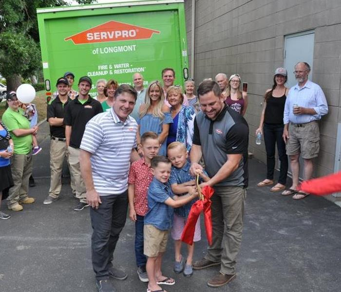 a group of people in front of a SERVPRO truck